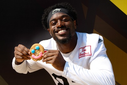 Hamilton Tiger-Cats pose with Tim Hortons Smile Cookies, purchases made that day support local charities